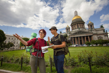 Young hikers are looking at the map and discuss the way