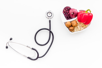 Products good for heart and blood vessels. Vegetables, fruits, nuts in heart shaped bowl near stethoscope on white background top view copy space