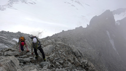 mountain guide and client heading towards a high alpine summit on a foggy day