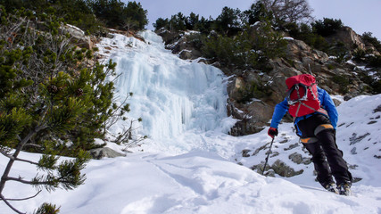 male ice climber in a blue jacket and red backpack approaches an ice fall on a beautiful winter day adn prepares to climb it