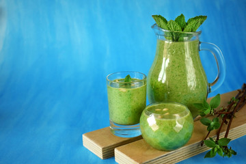 Green smoothie in glass vessels and on blue background. Copy space