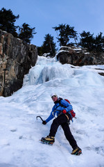 male ice climber in a blue jacket on a gorgeous frozen waterfall climbing in the Alps in deep winter