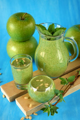 Green smoothie in glass vessels and apples on blue background