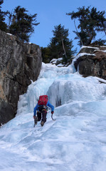 male ice climber in a blue jacket on a gorgrous frozen waterfall climbing in the Alps in deep winter