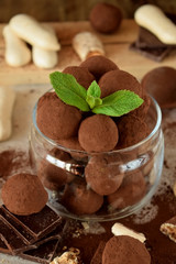 Chocolate truffles sprinkled with cocoa powder in a glass jar