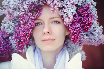 Outdoor fashion photo of a beautiful young blue-eyed woman. Spring color. beautiful blonde girl in lilac flowers. Perfume with a scent of flowers. Perfumes and beauty