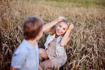 Young blonde beautiful mother walking with her smiling son on the golden field. Happy family and sunny day