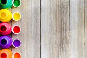 Colorful open paint bottels on rustic wooden background with copy space, top view/arts and crafts background concept
