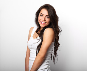 Beautiful positive happy laughing woman in white shirt with toothy smile holding the hand the long brown hair on white background.
