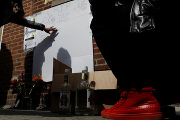 A woman touches a makeshift memorial near where New York police officers shot to death an unarmed black man who pointed a metal pipe at them, in the Crown Heights section of Brooklyn