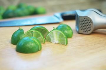 Cut key limes on cutting board with garlic press