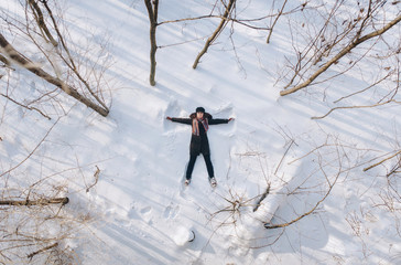 A girl on the snow shows an angel. Spreading arms. Top view. Drone.
