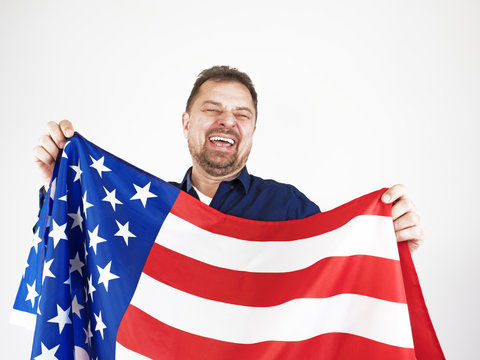 Very emotional American patriot young man holding National Flag of the United States of America celebrating Independence Day on 4th of July