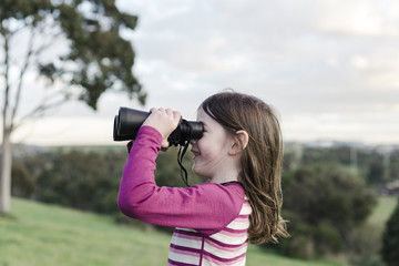 Side view of girl looking through binoculars while standing at park against cloudy sky
