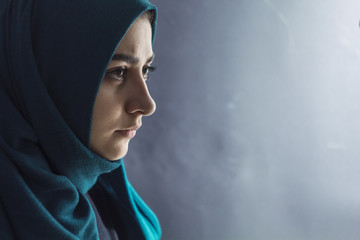 Sad Muslim girl hijab on a black background. Arab young woman face in profile, copy space.