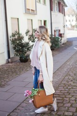 Young beautiful blond woman walking through the spring city. Cute young woman holding a bouquet of tulips. Spring. Fashion.