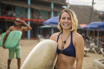 Portrait of happy woman in bikini holding surfboard while standing at beach