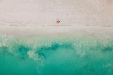 Drone photo. The couple lies on the beach