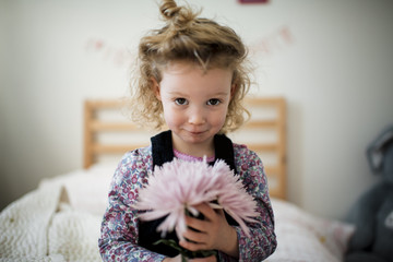 Portrait of cute girl with gerbera in bedroom