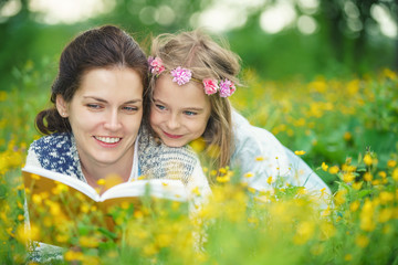 Mother and daughter lying on spring meadow enjoy reading book