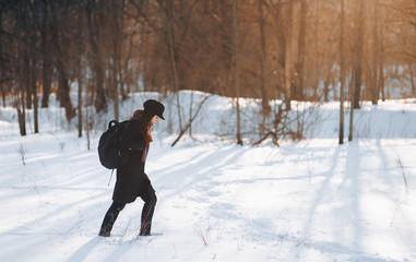 A girl with a backpack in the winter forest walks through the snow. Walk alone in frosty weather. Snowdrift.