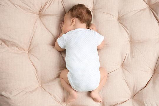 Cute newborn baby sleeping on lounge at home