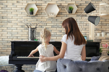 Little girl with teacher learning to play piano indoors