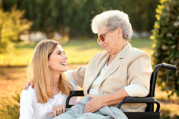 Senior woman in wheelchair and nurse from care home outdoors