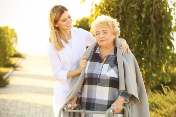 Senior woman with walkers and nurse from care home in park