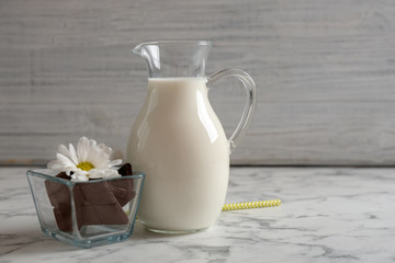 Jug with milk and chocolate pieces on table