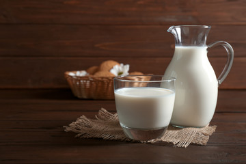 Glass and jug with milk on wooden table
