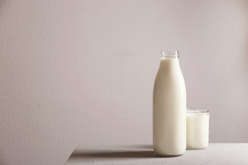 Bottle and glass with milk on table against grey wall
