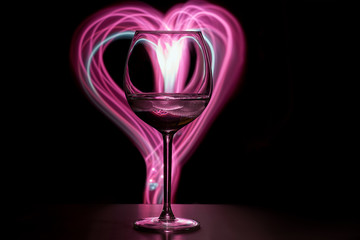 Wine glass on the table, in the background a pink heart