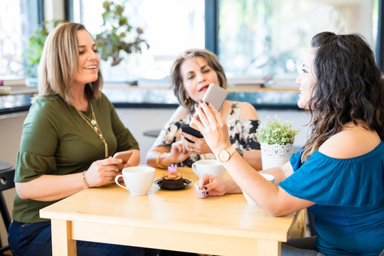 Woman showing her mobile phone to friends at cafe