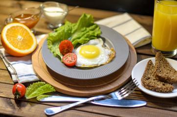 English Breakfast: fried egg, juice, cherry tomatoes, lettuce, grain bread, sauce, top view.