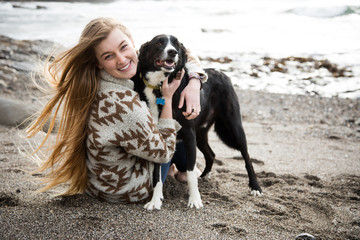 Woman hugs dog at beach