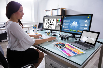 Female Designer Working On Multiple Computer