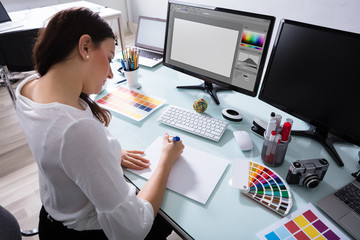 Female Designer Drawing On Blank Placard