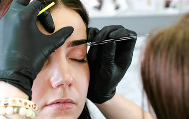 Cosmetologist performs the procedure of correction eyebrow with tweezers. Front closeup view.