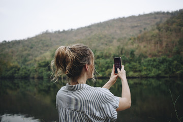 Closeup of a woman hand raising her smartphone up taking a photo of nature travel and tourism concept