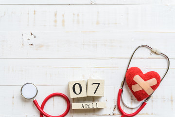 Wooden Block calendar for World health day, April 7. Healthcare and medical concept. Red heart with Stethoscope on Pastel white and blue wooden table background texture.