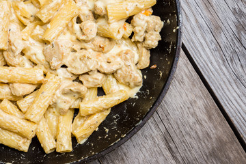 Creamy pasta with chicken and mozzarella cheese in pan. Selective focus.