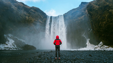 Wall Mural - Skogafoss waterfall in Iceland. Guy in red jacket looks at Skogafoss waterfall.