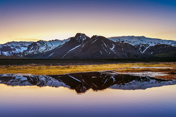 Wall Mural - Winter mountains reflection at sunset in a lake.