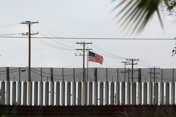 The U.S. flag flies behind the current border fence in this picture taken from the Mexican side of the border in Tijuana
