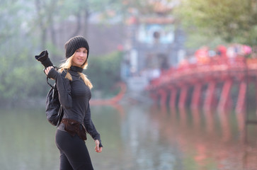 Outdoor summer smiling lifestyle portrait of pretty young woman having fun in the city in Vietnam  with camera, travel photo of photographer making pictures
