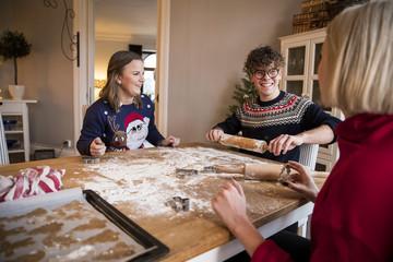 Three people preparing gingerbread cookies