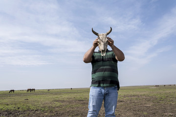 Young man holding a cow skull in front of his head low angle view point