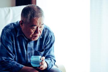 窓際の椅子に座っている高齢者男性