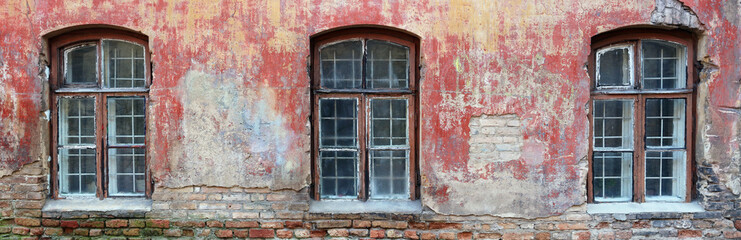 Three rotten curved windows in the red wall of a ruined old brick house.